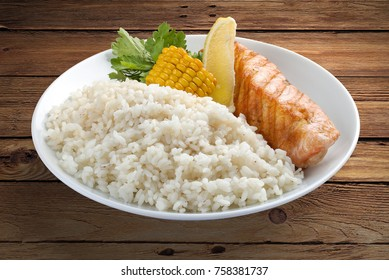 Rice porridge with salmon and vegetables on a wooden background