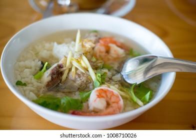 Rice porridge with shrimp and pork in white bowl breakfast on wooden table