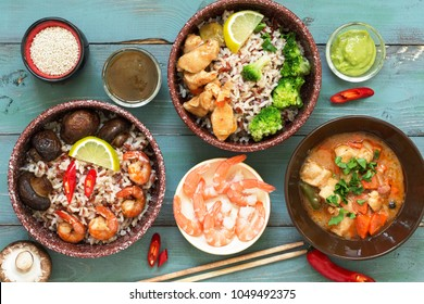Rice with prawns, chicken, mushrooms, broccoli on a naked rustic background. Asian dishes. Concept of Asian food. View from above