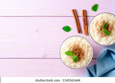 Rice pudding with cinnamon and mint on light purple wooden background. Top view. Copy space.