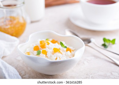 Rice pudding with dried apricots in small white bowl
