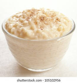 Rice pudding sprinkled with nutmeg in an individual glass bowl.