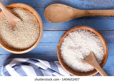 Rice and quinoa in wooden bowls on a blue wood table with tea towel and wooden spoon. Flat lay from directly above.