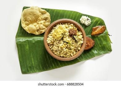 Rice and roasted fish in a pan. Kerala Uruleeloottu, Uruliyil oottu