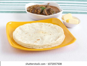 Rice roti or flat bread made from rice flour dough, a south Indian vegetarian, traditional and popular food, is usually eaten for breakfast with eggplant or brinjal curry and butter.