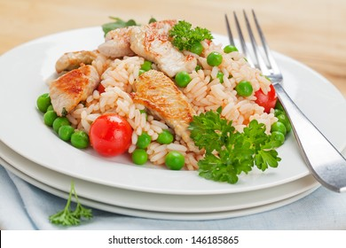Rice salad with turkey breast, tomatoes, peas and parsley on a brown wooden plate