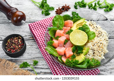 Rice with salmon, avocado and spinach. In a black plate on a wooden background Top view. Free space for your text. Flat lay