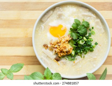Rice soup with meat, egg and herbs on wooden board with copy space.