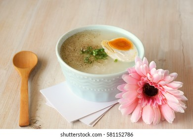 rice soup with salted egg and spring onion in bowl with pink Gerbera
