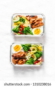 Rice, stewed vegetables, egg, teriyaki chicken - healthy balanced lunch box on a light background, top view. Home food for office concept. Copy space