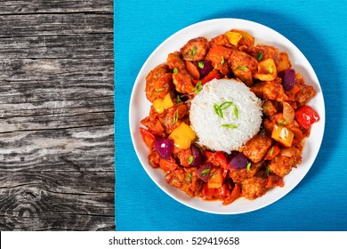 rice with Sweet and Sour fried pork chunks with vegetables, sprinkled with green onion on white dish on table mat on dark wooden planks, view from above