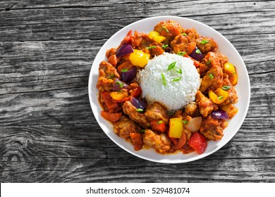 rice with Sweet and Sour fried pork chunks with vegetables, sprinkled with green onion on white dish on dark wooden boards, view from above