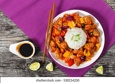 rice with Sweet and Sour fried pork chunks with vegetables, sprinkled with green onion on white dish on table mat with chopstick on dark wooden boards with soy sauce and slices of lime, top view
