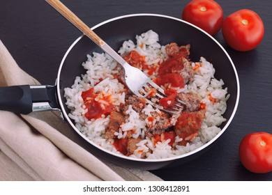 Rice with turkey minced meat and organic tomato sauce in frying pan. Close up.