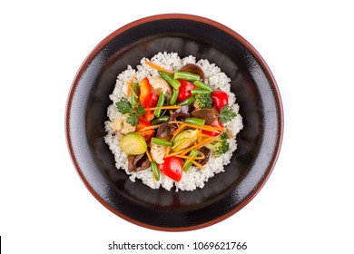 Rice with vegetables in a black bowl on a white background. Garnish. Isolated.