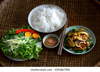 Rice vermicelli with grilled fish ball. Pan-fried fish with onion, rice vermicelli, mint leaves, fried shallots, peanuts, pickles, sweet and sour chili sauce