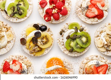 Rice wafers with a variety of fresh fruits, seeds, nuts and cream cheese on a white background, top view. Rice cakes, the concept of a healthy breakfast or dessert
