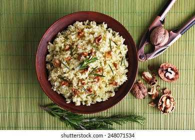 Rice with walnuts and rosemary in plate on bamboo mat background