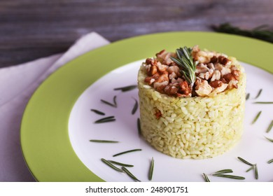 Rice with walnuts and rosemary in plate on rustic wooden planks background