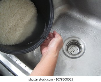 Rice wash before cooking. Rice is the main food of Asian people. Electric rice Cooker and hand's housemaid.
