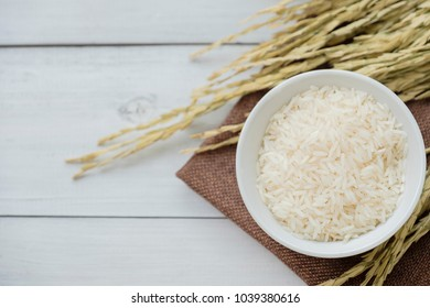 Rice in white bowl with yellow rice plant on wooden background.
