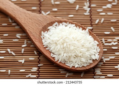 Rice in a wooden spoon on bamboo napkin. Close-up.
