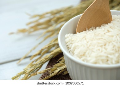 Rice and wooden spoon in white bowl with yellow rice plant on wooden background.