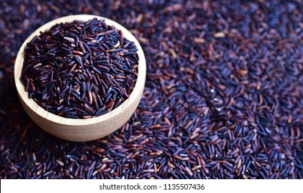 Riceberry (rice berry) which is a registered rice variety from Thailand in wooden bowl on blurry riceberry background with long copy space for text, healthy and clean food concept