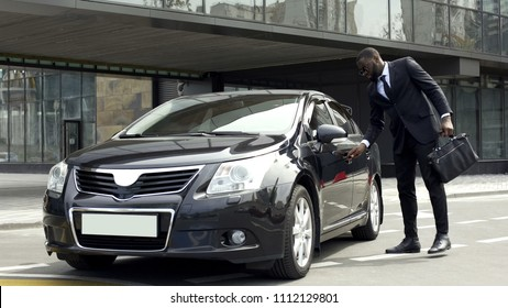 Rich African American man opening door of luxury car with special key, security