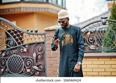 Rich african man in stylish traditional clothes and hat posed outdoor background his mansion, speaking on mobile phone.