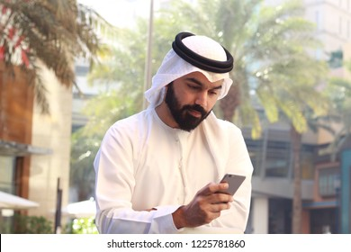 Rich Arab Business Man Using Mobile  Phone And Wearing UAE Traditional Dress, Palm Tree In Background
