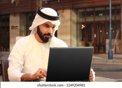 Rich Arab Business Man Using Technology And Wearing UAE Traditional Dress ( Technology Business Person )