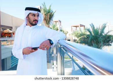 Rich Arab man looking for away with mobile phone device wearing traditional middle east gulf men's wear - kandora