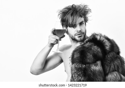 Rich athlete enjoy his life. Guy attractive rich posing fur coat on naked body. Sexy sleepy rich macho tousled hair drink wine isolated on white. Health and wellbeing. Richness and luxury concept.