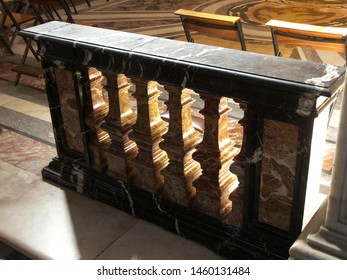 A rich banister is located inside a church. The banister is made of black and red marble. The surface of the banister is shining.