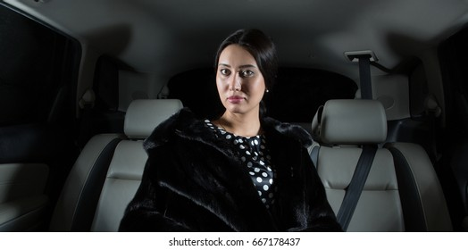 Rich, beautiful, elegant, young woman in a fur coat in a limousine