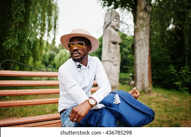 Rich black man sitting on bench at golden sunglasses and hat