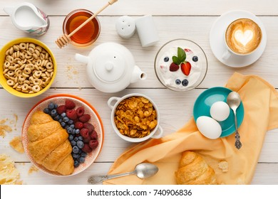 Rich breakfast menu background. French crusty croissants, muesli, yogurt, coffee, berries, honey and boiled eggs for tasty morning meals on wooden table, top view