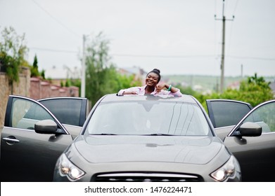 Rich business african woman in silver suv car on sunroof having fun.