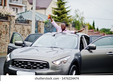 Rich business african woman in silver suv car on sunroof having fun with beer at hand.