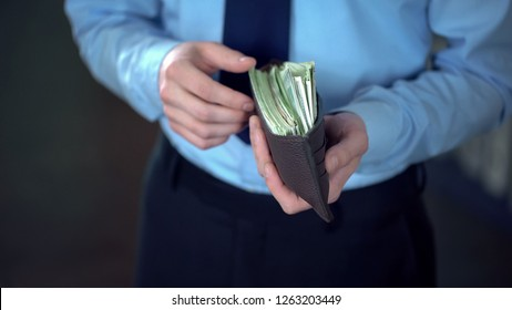 Rich businessman holding opened leather wallet full of dollar banknotes, finance