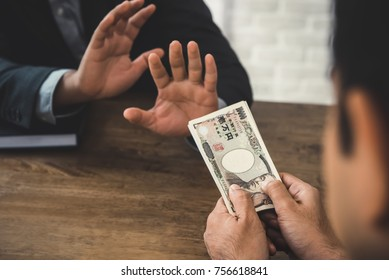Rich businessman offering Japanese yen money banknotes to the another person, but he refusing - anti birbery and corruption concept