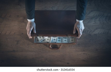 Rich businessman opening a leather briefcase filled with dollar packs, top view, unrecognizable person