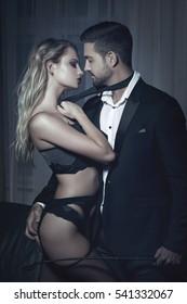 Rich businessman with whip hold by tie blonde lover in underwear, bdsm