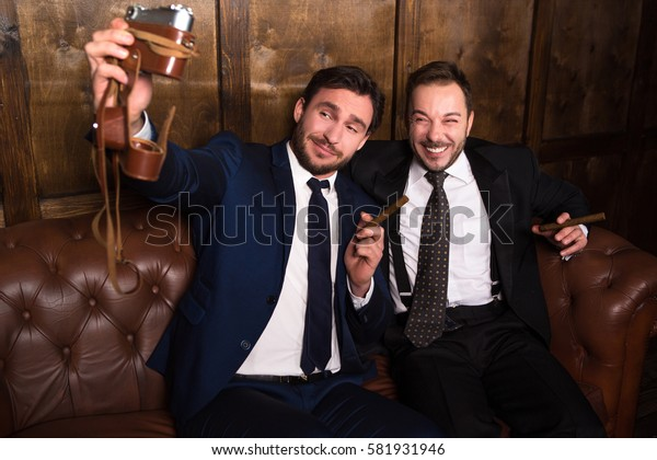 Rich businessmen with cigars making photos while spending time in restaurant. Russian business people drinking alcohol and making money.