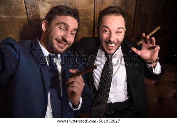Rich businessmen with cigars smiling for camera. Luxury people spending free time in restaurant. Happy friends looking at camera.