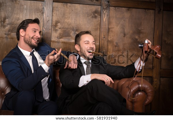 Rich businessmen making self photos while sitting on sofa in restaurant. Handsome rich men with cigars smiling for camera.