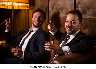 Rich businessmen resting and relaxing in men's club. Happy men drinking whiskey and smoking cigars. People looking at camera.