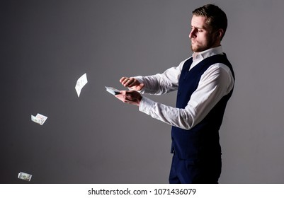 Rich and carefree concept. Successful entrepreneur on arrogant face wasting money. Banknotes, cash dollars fly in air around guy. Man in formal wear, businessman throwing money on grey background.