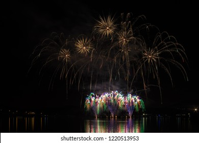 Rich and colorful fireworks over surface of Brno's Dam with lake reflection